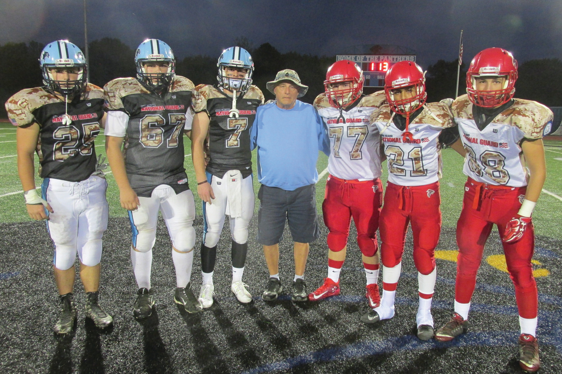 "CAPTAIN'S CORNER: Don Iafrate, center, a 1967 Johnston High grad, was given the distinction of performing the coin toss prior to last Friday's ""Salute to Service."" He served 43 years and six months in the National Guard, and is joined here by each team's captains."