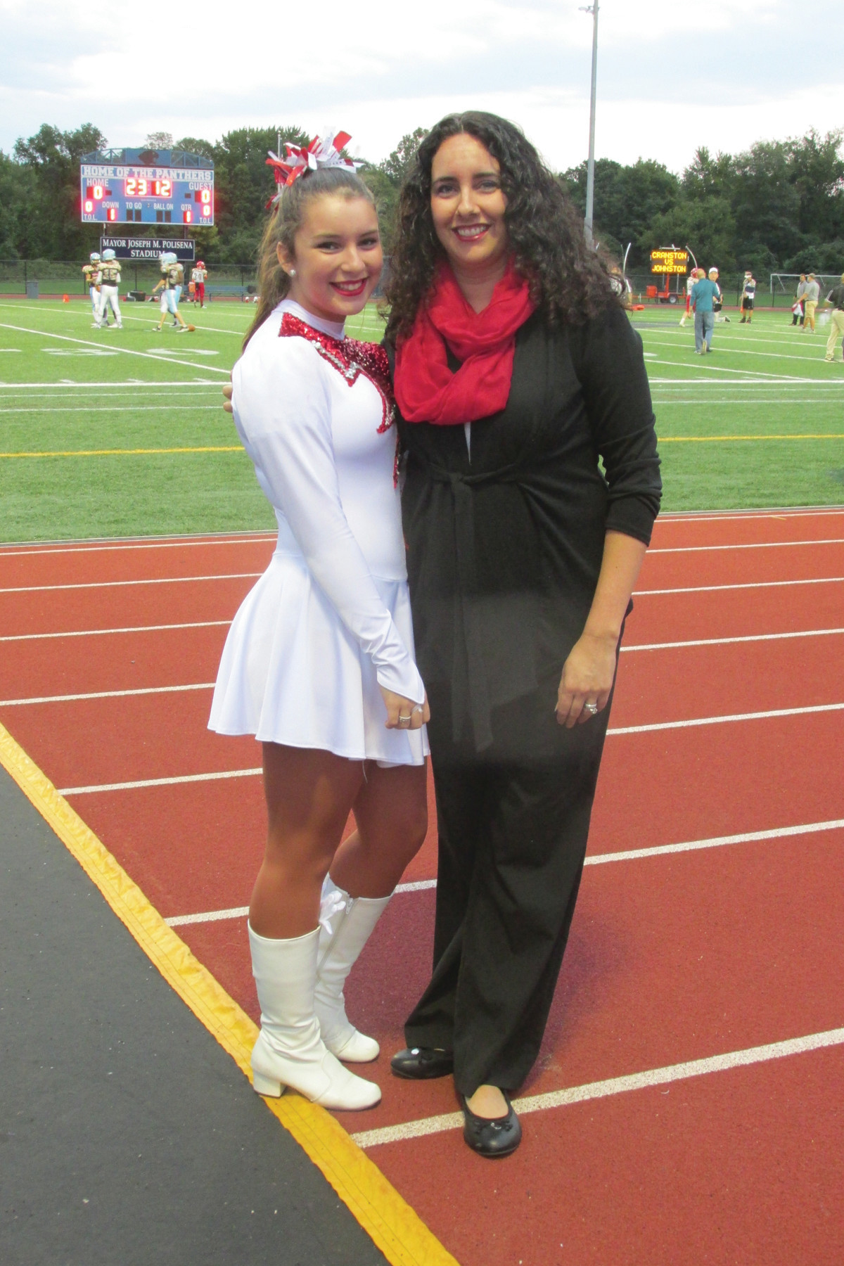 "DOUBLE DUTY: Cranston West Falconettes coach Christine Baum, right, who is a 1994 Johnston High School grad, joins Reegan Moretti of her dance troupe prior to last Friday night's ""Salute to Service."""