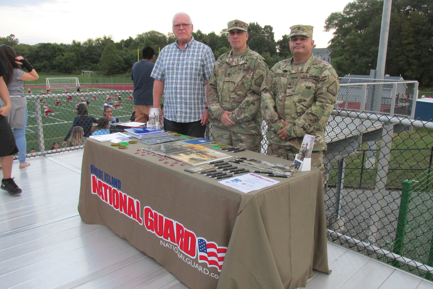 "LINKED LEADERS: Johnston High Principal Dennis Morrell, left, greets Rhode Island National Guard Sgt. First Class Jason Blouin, center, and Sgt. Paul Cataldo, right, during last Friday night's ""Salute to Service."""