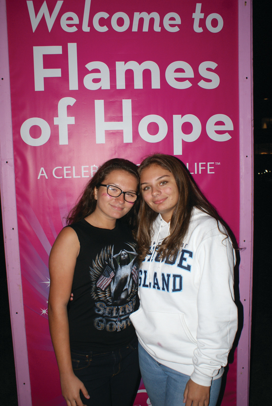 WELCOME ALL: Pictured in front of just one of the many banners welcoming the public to the Gloria Gemma Breast Cancer Resource Foundation's Flames of Hope are twin sisters Madison and Katrini Abatiello, who attend Cranston High School East.