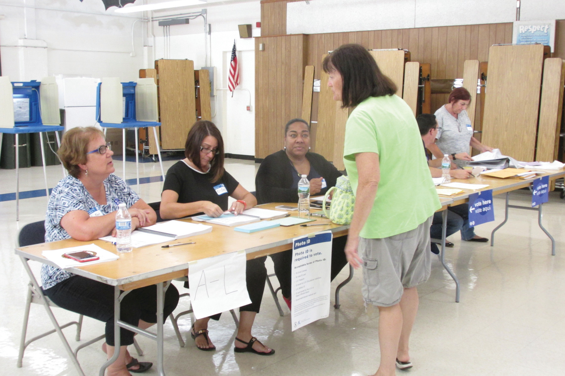 CHECKING IN: A voter checks in with workers who staffed the polling place at Sarah Dyer Barnes Elementary School.