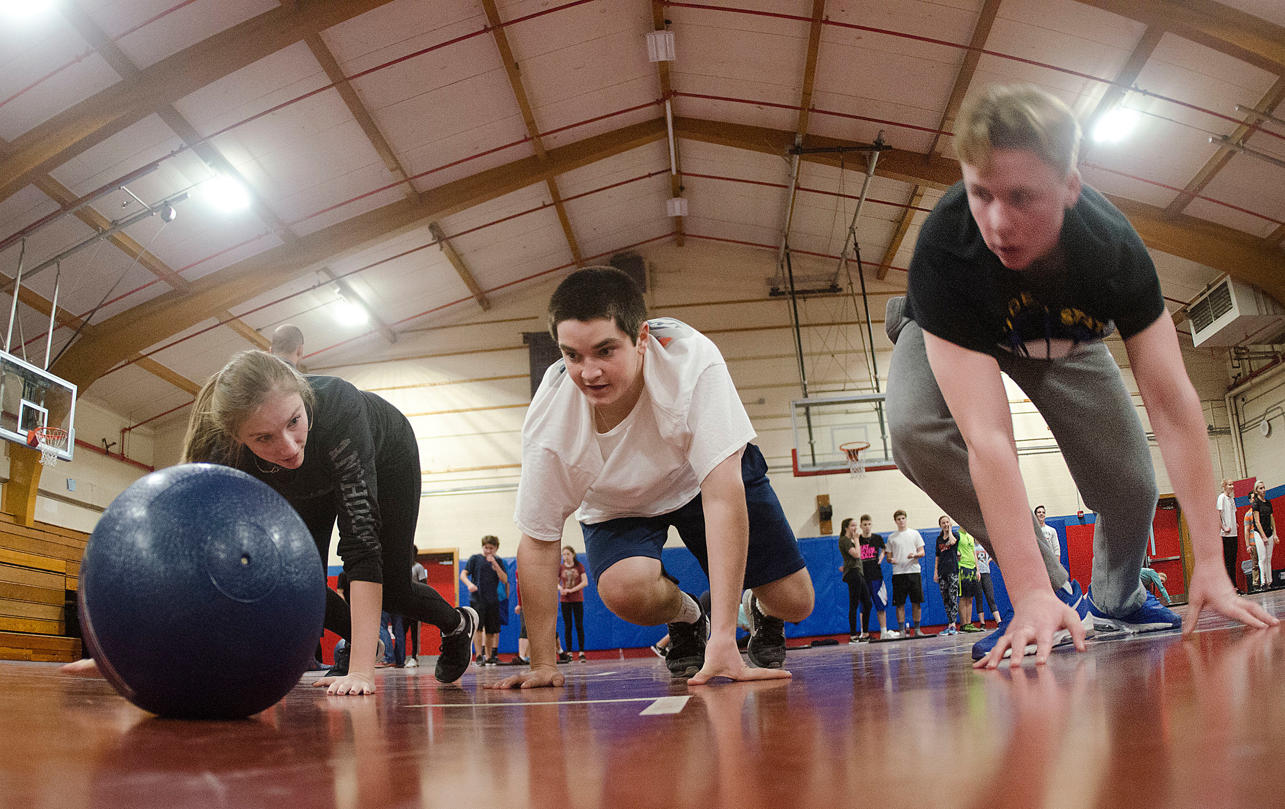 Kelly Conley, Noah McHugh and Conner Stone (from left) bear-crawl across the floor during a drill.