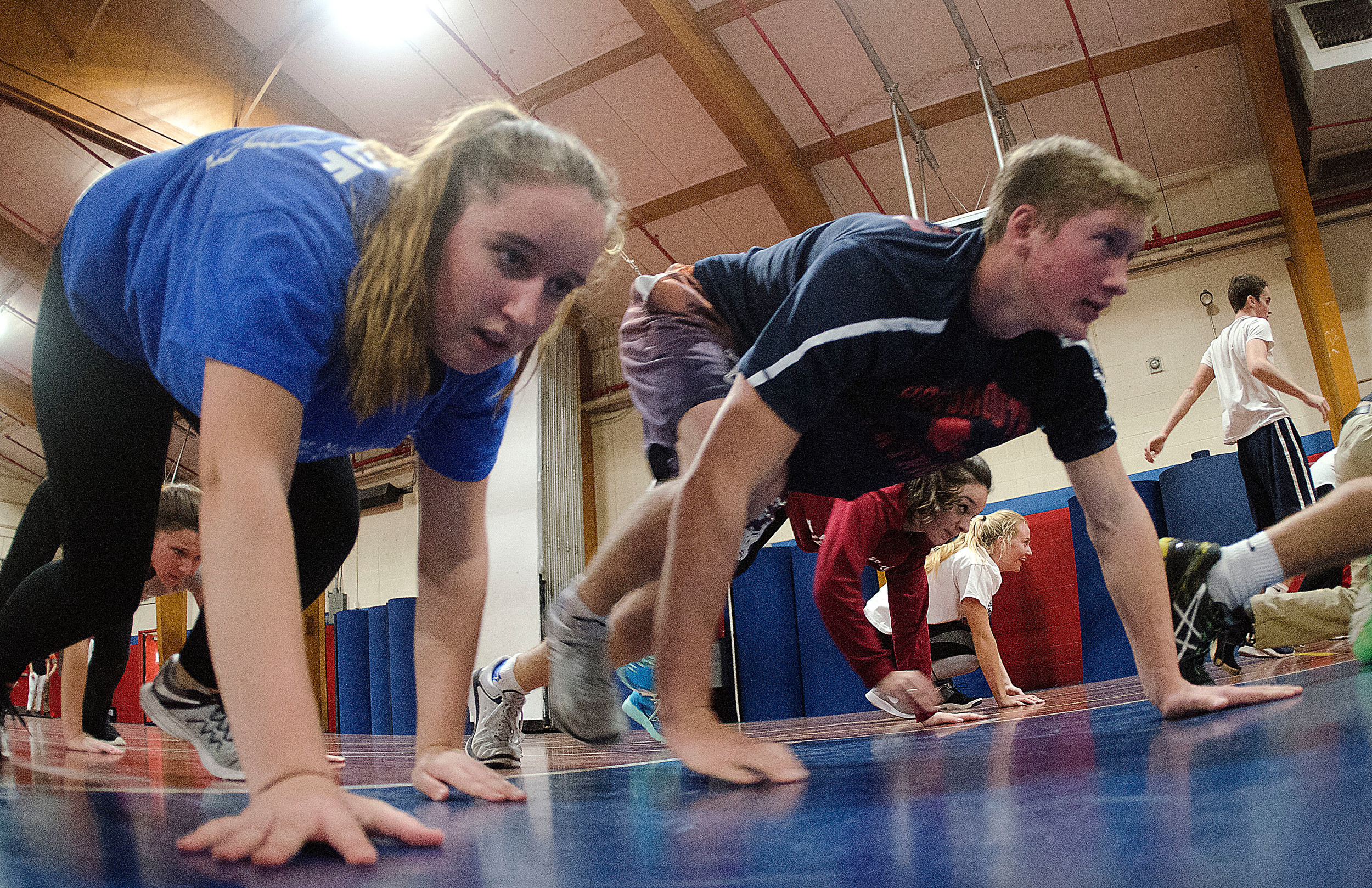 Jami Silveira and John Boruch bear crawl across the gymnasium during a drill.