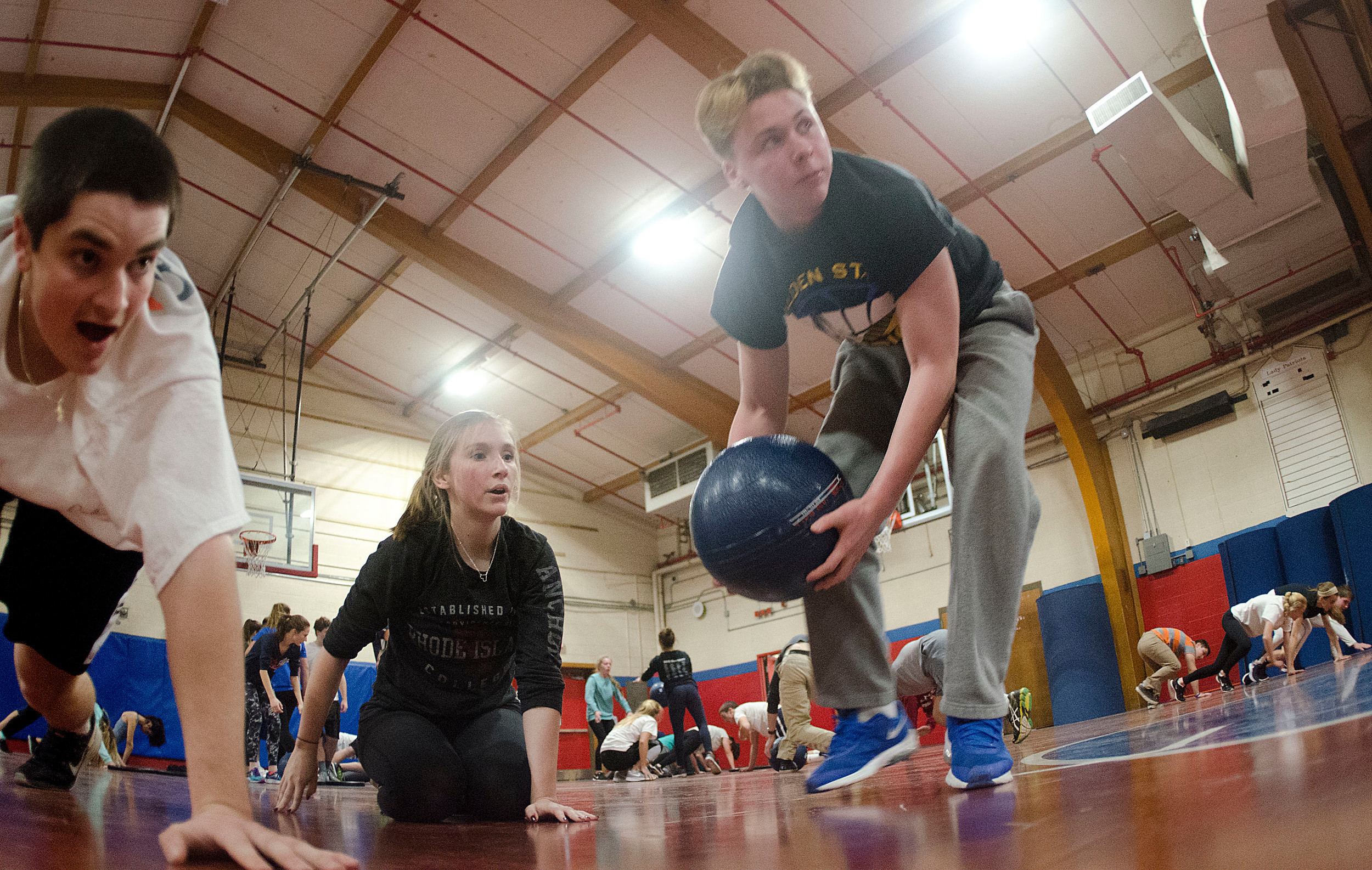 Noah McHugh, Kelly Conley and Connor Stone race across the gym against the other teams, bear-crawling and heaving a giant medicine ball during a drill.