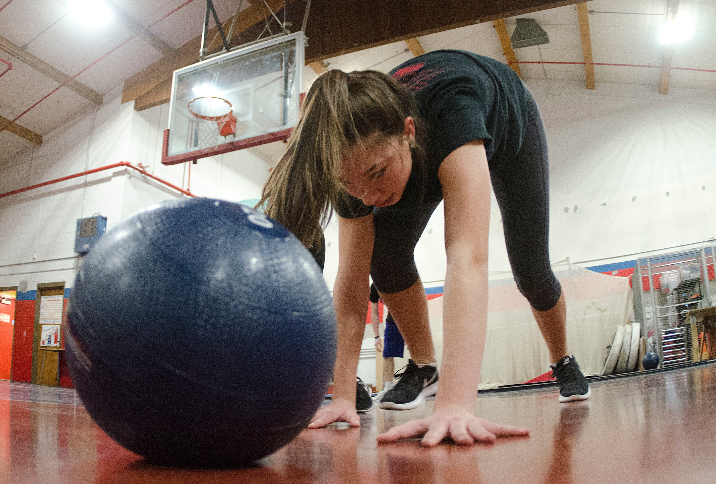 Kylie Swider bear-crawls to a giant medicine ball during a drill.