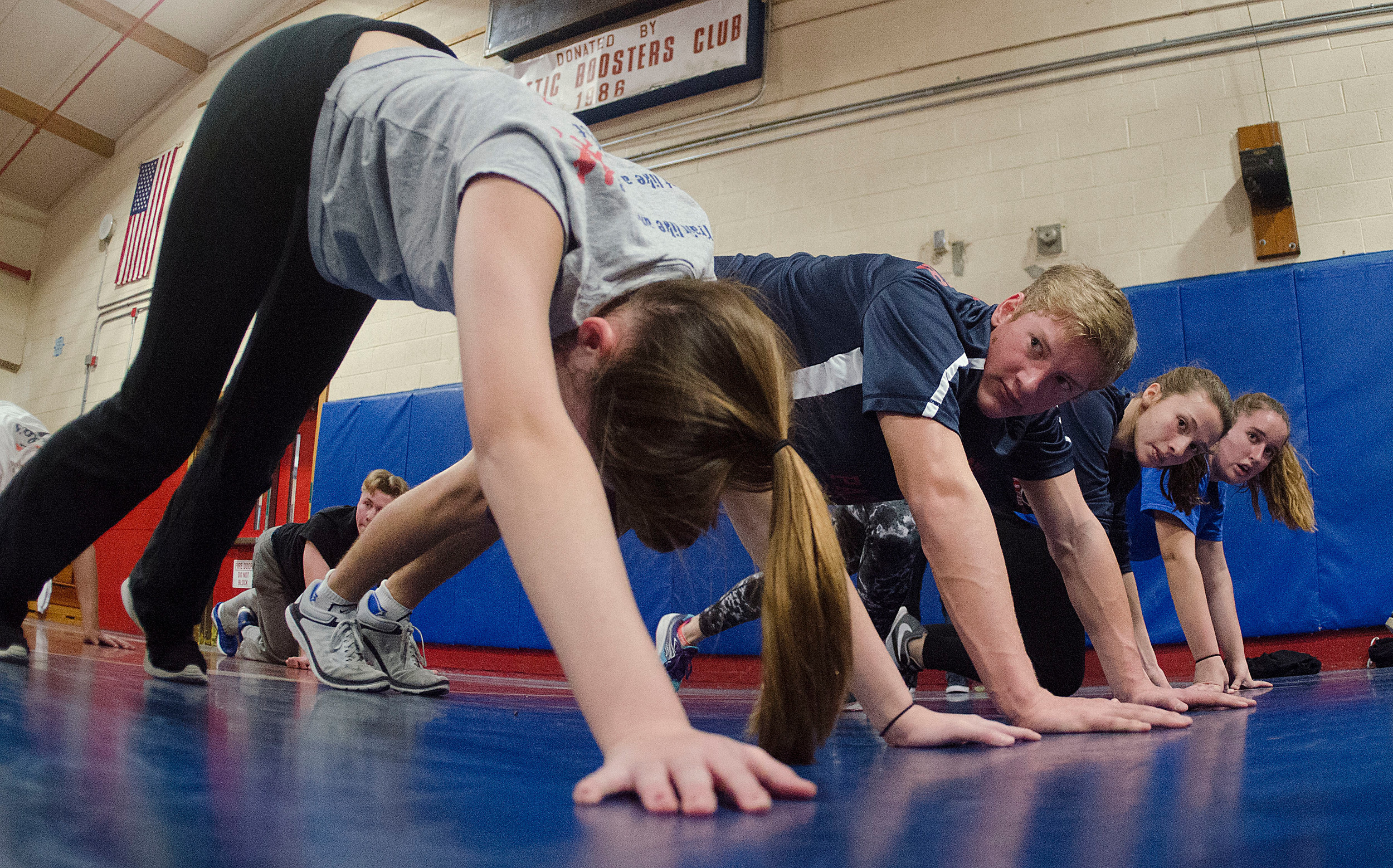 John Boruch (middle) looks on while his team holds a plank position during a drill.