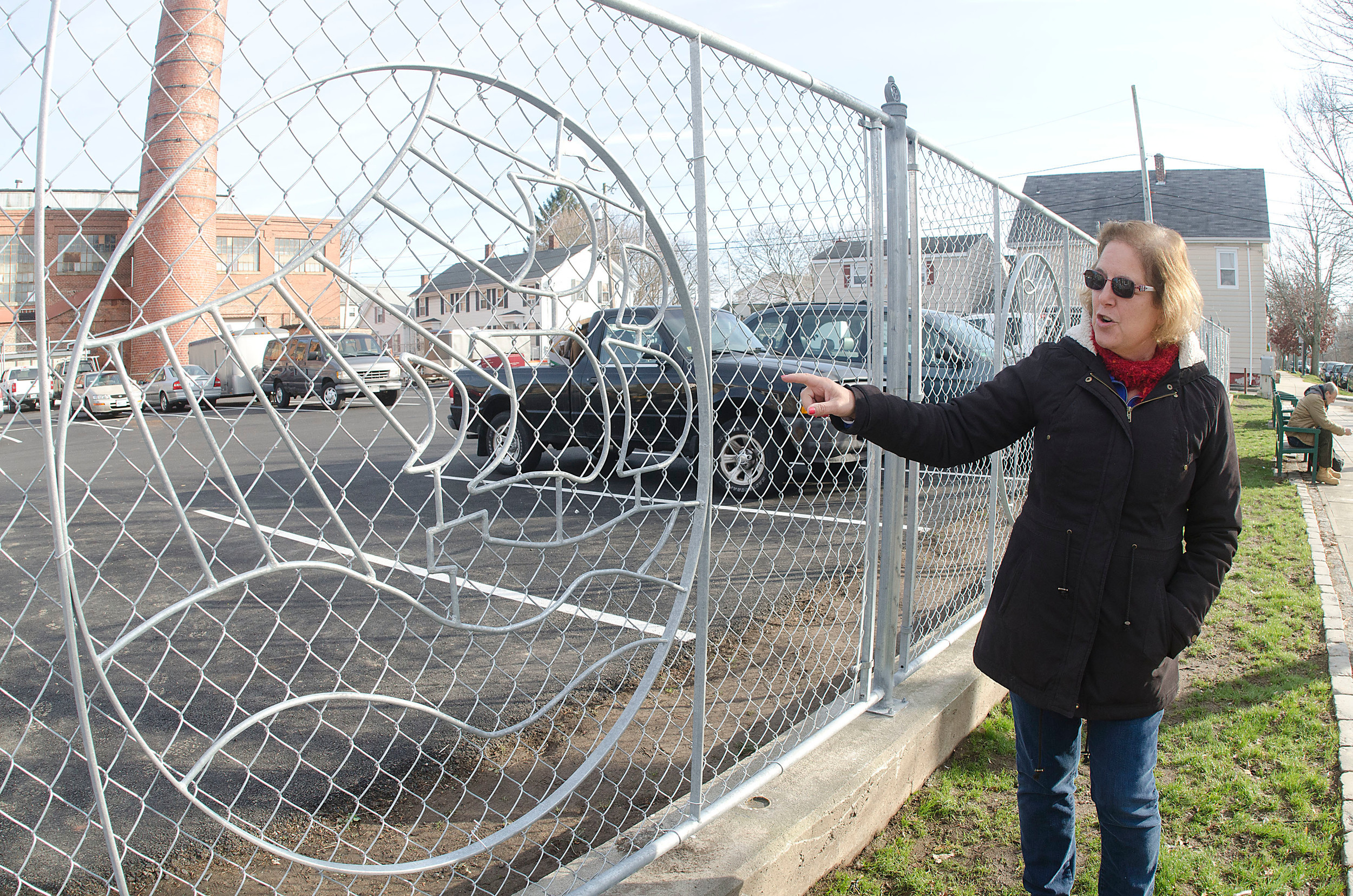 Mosaico Executive Director Diana Campbell shows the decorative fence that was recently erected along Wood Street. Medallions on the fence represent slices of life around Bristol.