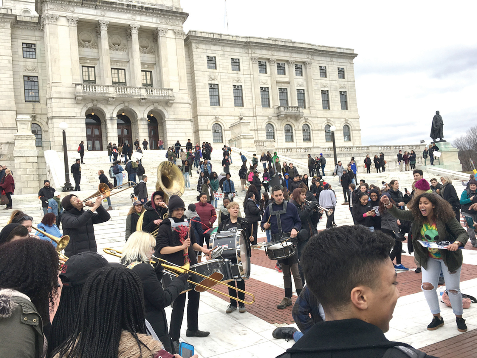 EXPRESSIONS OF HOPE: A band plays and students dance in front of the State House.
