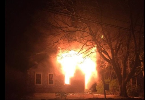 Flames erupt from the windows of the Old Harbor Road house minutes after firefighters arrived early Saturday. Westport Fire Department photo.