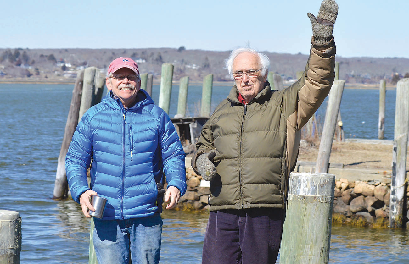 Jim Whitin, chairman of the Westport Planning Board, and David Cole of the Westport Watershed Alliance stand on town docks that are predicted to be deep underwater by century's end.  Tides would rise above Mr. Cole's outstretched arm. The two have launched the South Coast Climate Change Coalition in hopes of helping prepare for the changes to come.