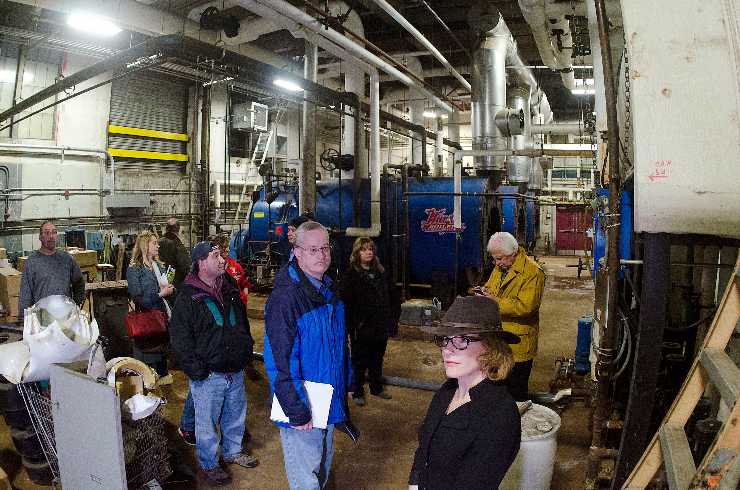 East Providence mayor James Briden (center) and finance director Lucy Maddock and members of the council and school committee take a long look around at the East Providence High School boiler room on Tuesday night during a walk through of the school.
