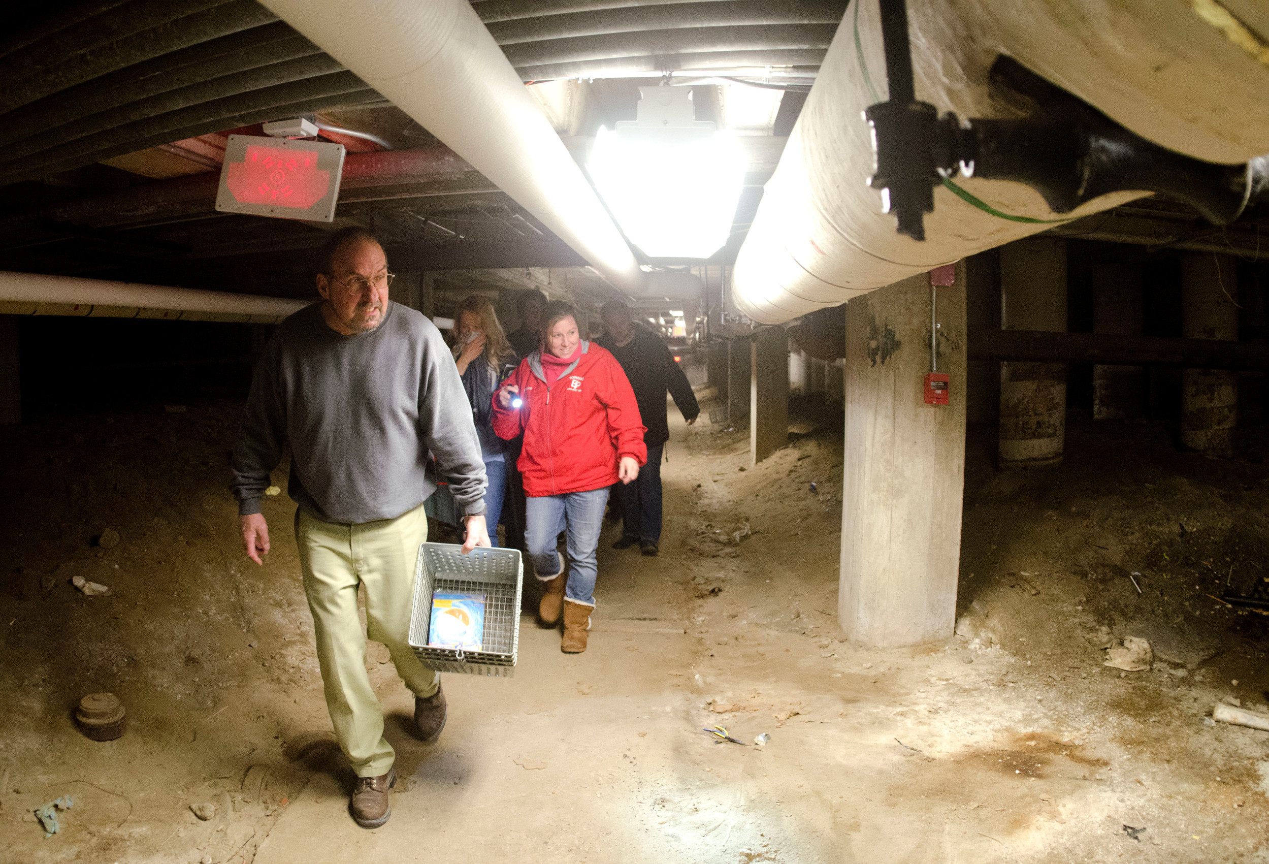 School committee members Anthony Ferreira and Jessica Beauchaine make their way through a dirt path under the 