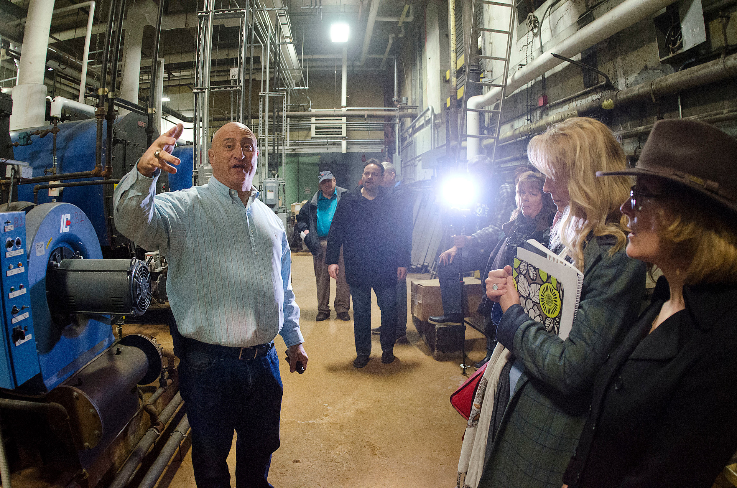 High school facilities director Tony Feola gives a tour of the school's boiler room to school committee and city council members. He explains that their is standing water underneath the boiler room.