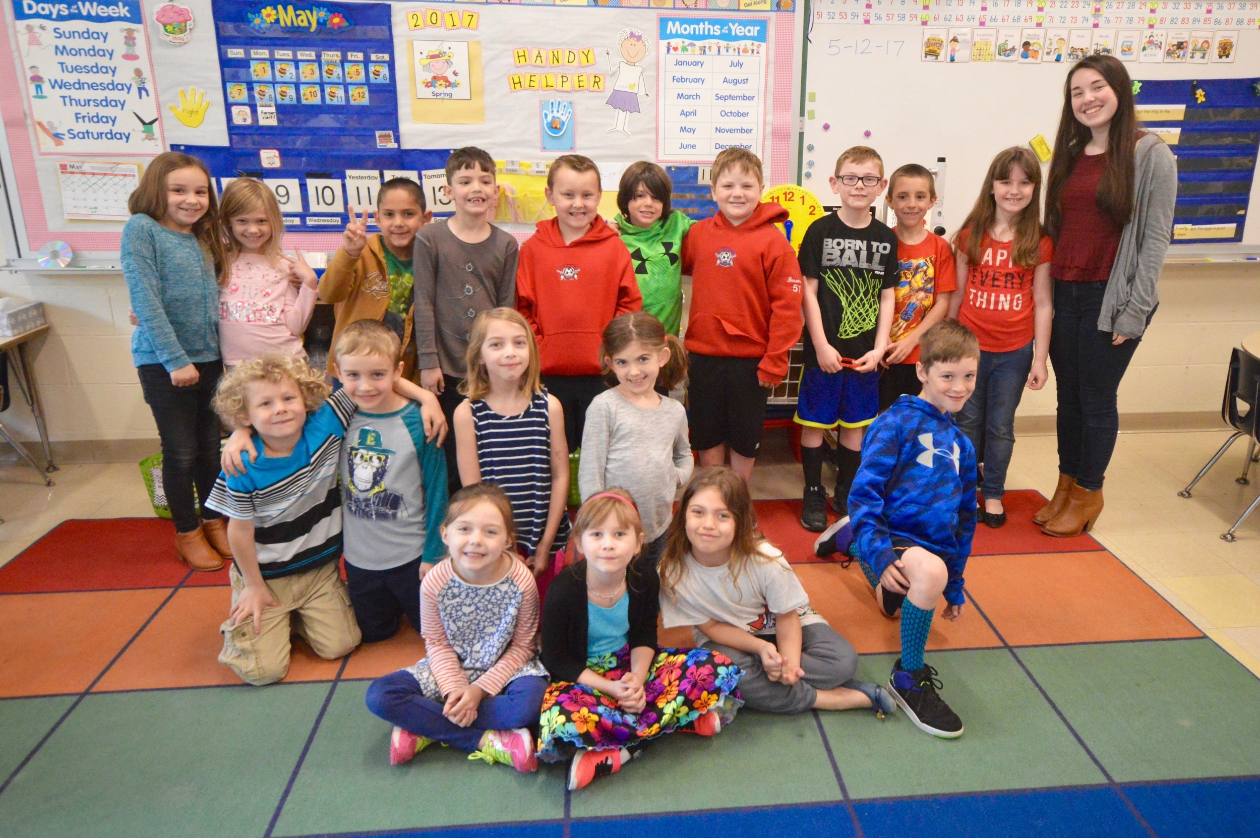 First-grade students in Diana Grinnell's class at Hathaway School pose with Grace Dooley, a PHS senior taking child development classes who has been coming in and working with students on a periodic basis.