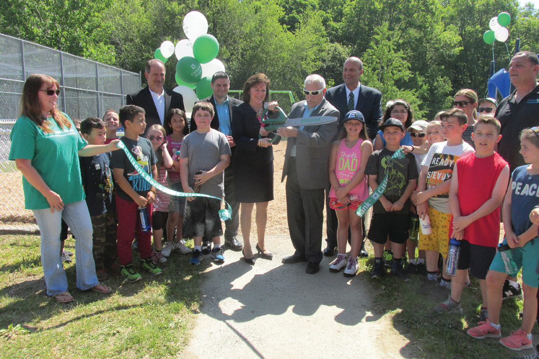 OFFICIAL RE-OPENING: Citizens Bank executive Barbara Cottam and Mayor Joseph Polisena used a pair of special oversized scissors to officially re-open the new playground at Woodlake Park in Johnston.