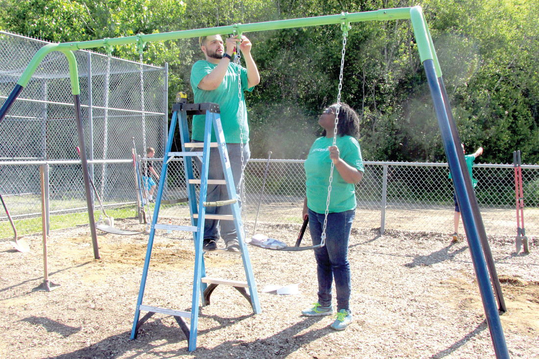 CLASSIC CONNECTION: Among the dozens of Citizens Bank employees who last weekend put the finishing touches on the renovated playground inside Woodlake Park were Guercy Carrie (left) and Ninenna Oronsaye who are putting together part of a new apparatus.