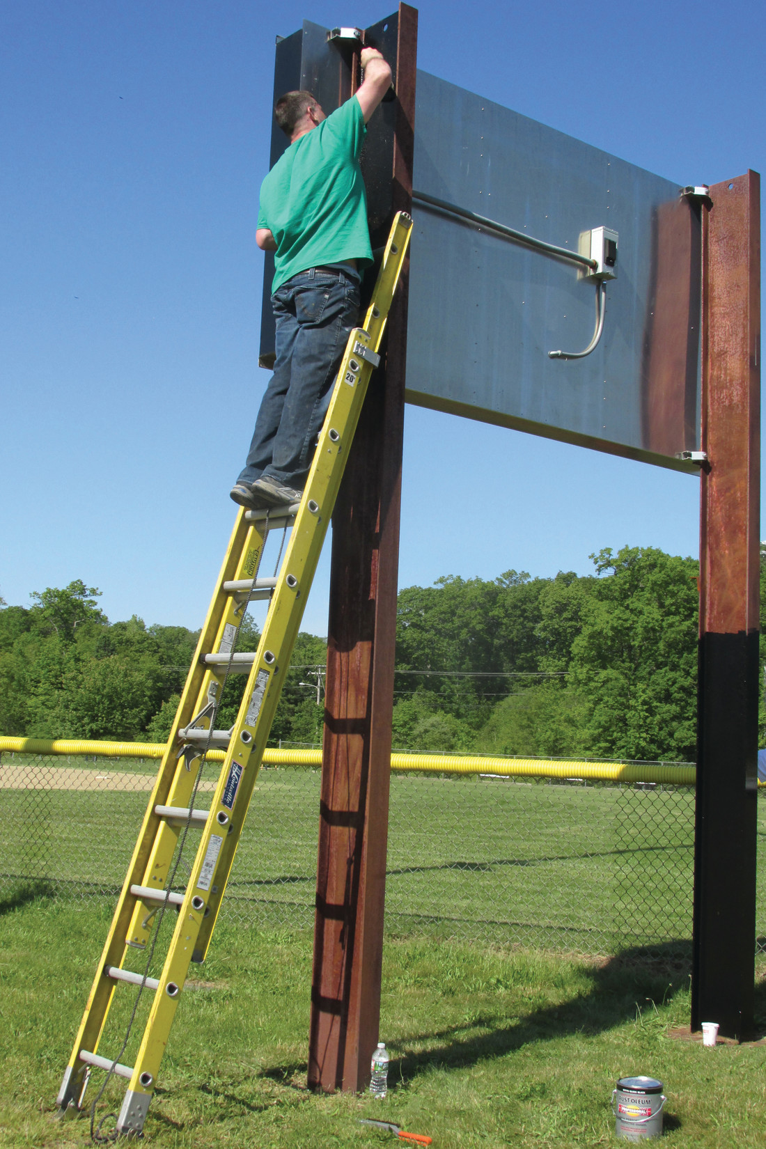 EXTENDED EFFORT: Citizens Bank staffer Ben Longtin used some extra effort – as well as an expandable ladder – to paint the steel support beam that holds the baseball scoreboard at Woodlake Park in Johnston. Sun Rise photos by Pete Fontaine