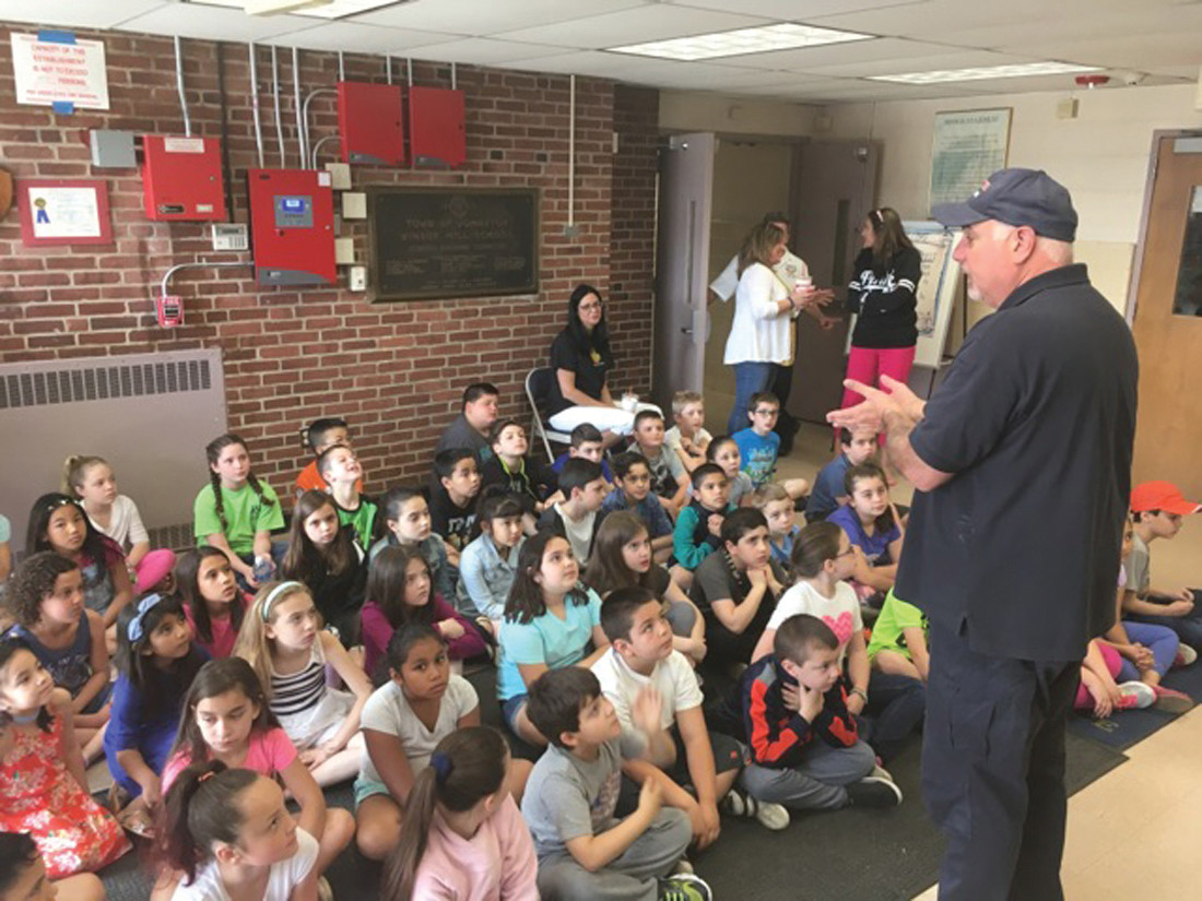 FRIENDLY FIREMAN: Students asked questions of members of the Johnston Fire Department about choking and what to do in an emergency.