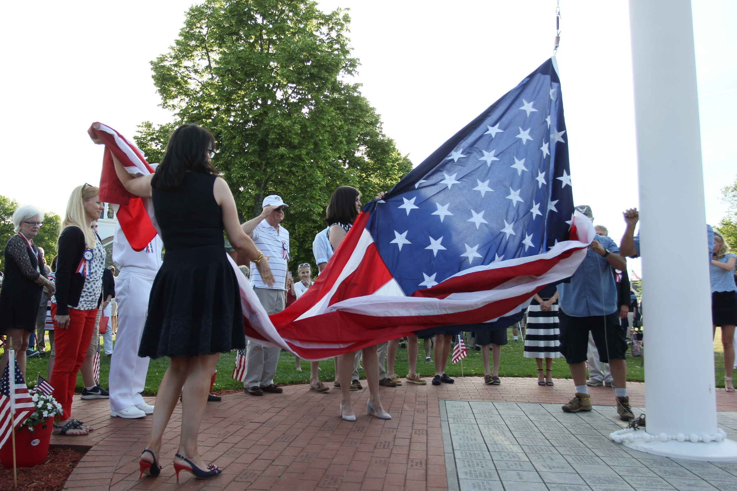 Chief Marshals Lisa Sienkiewicz and Gail Parella unfurl the American flag that now flies over Bristol Town Common.