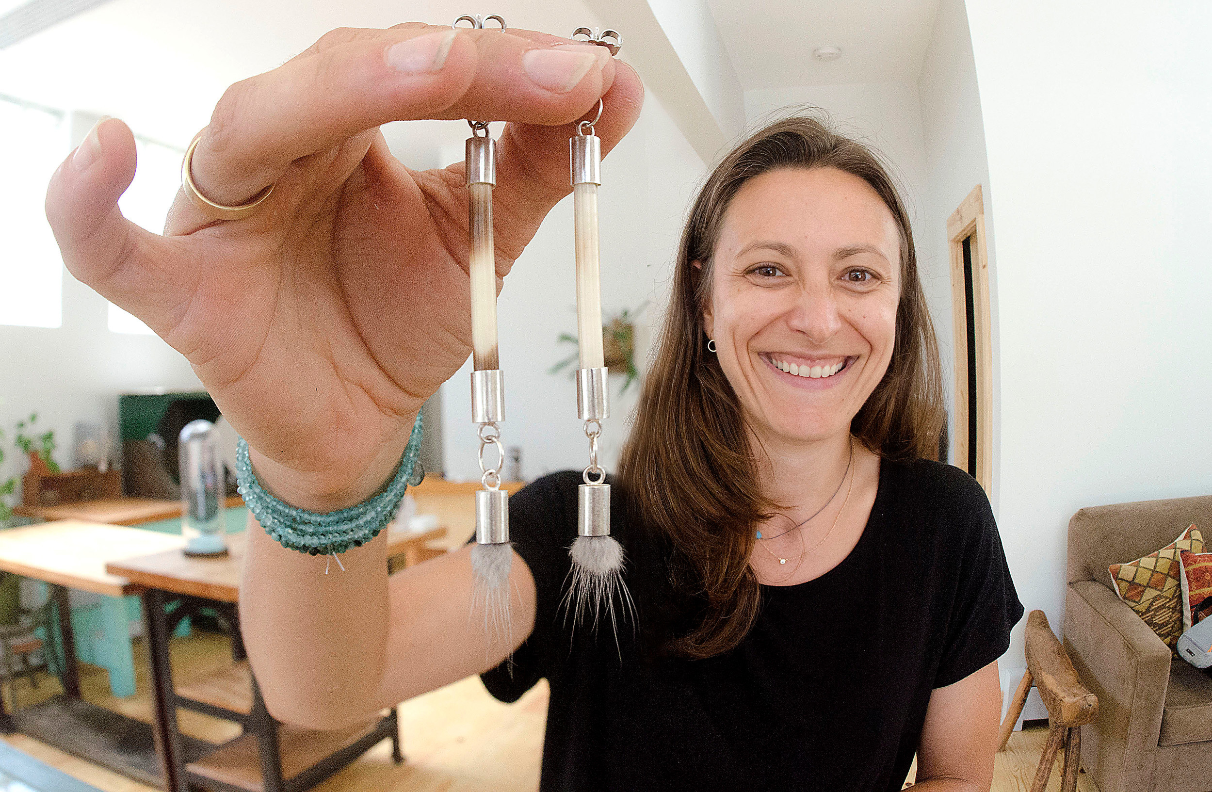 Artist and jeweler Kendall Reiss shows off a pair of earrings she crafted from porcupine quills and mink fur.