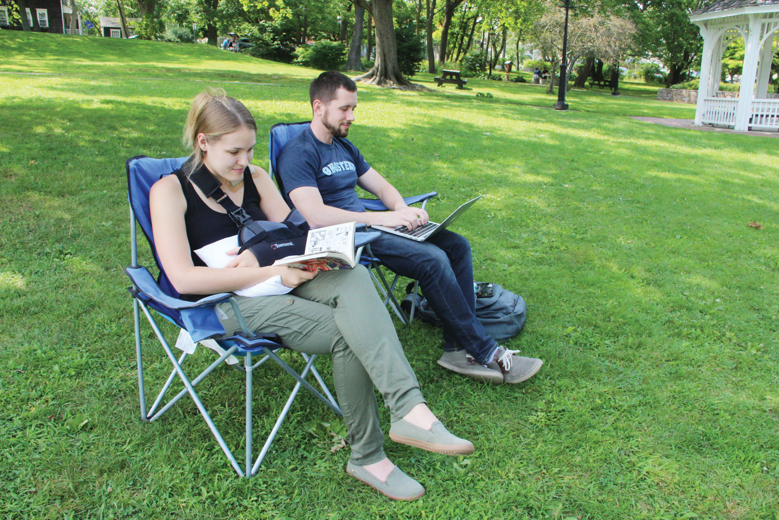 TWO FORMS OF PRINT: Amy Elsberger and Dave Counts found Pawtuxet Park as a good spot to do some book and computer screen reading Sunday.
