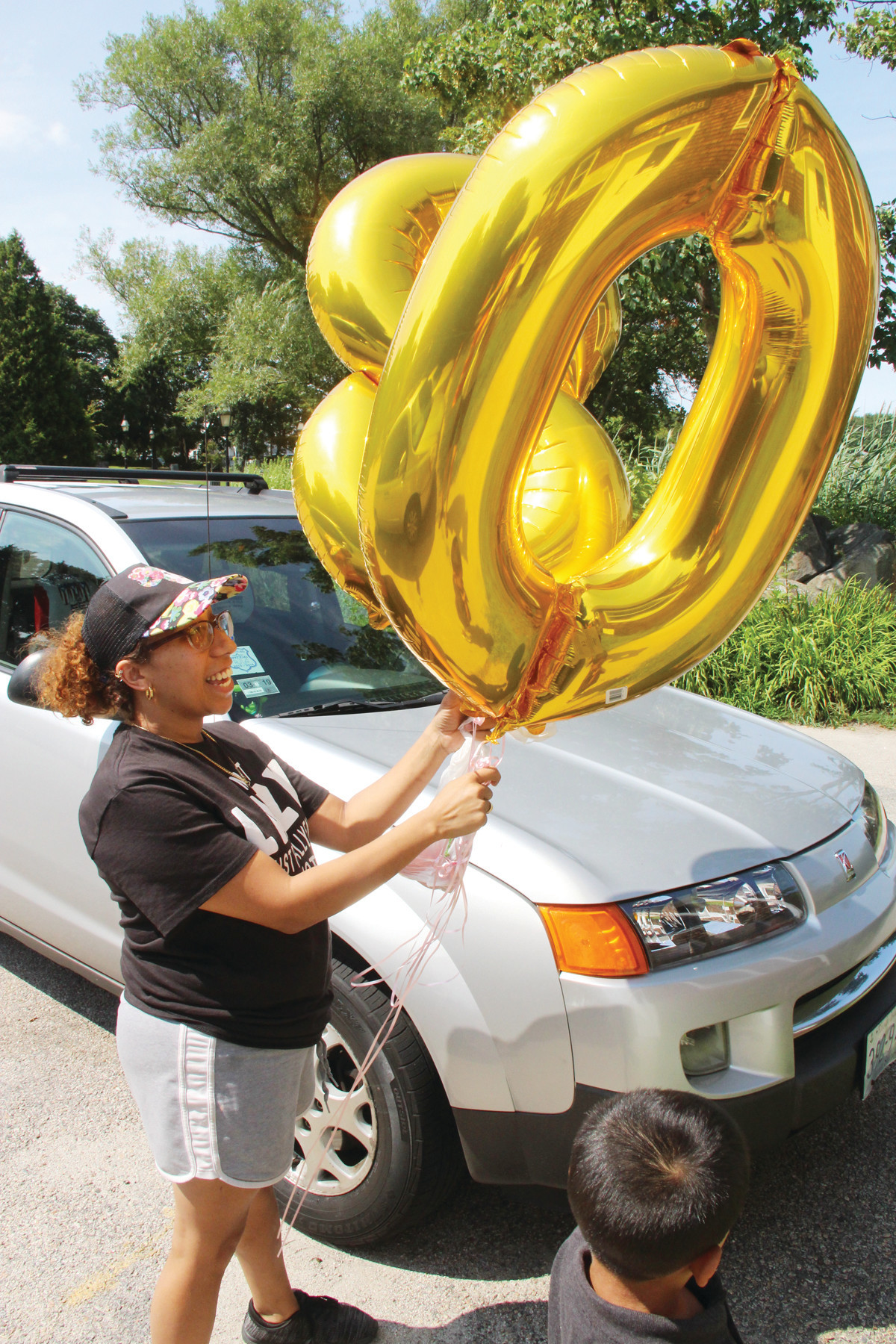 THE BIG 80: Massiel Garcia brings in balloons for the surprise 80th birthday party for Nereida Serrano held Sunday at the Aspray Boathouse in Pawtuxet.