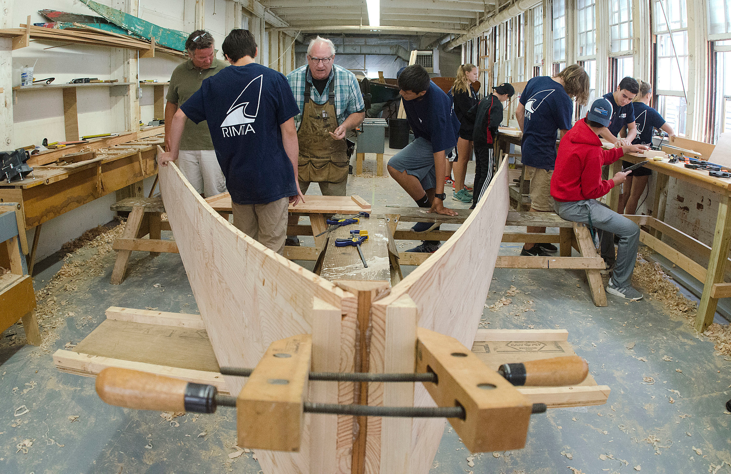 Boat builder Dan Shea (center) and Herreshoff Marine Museum Education Director Kirk Cusik work with a group of students on a Westport Skiff as part of a summer boat building program.