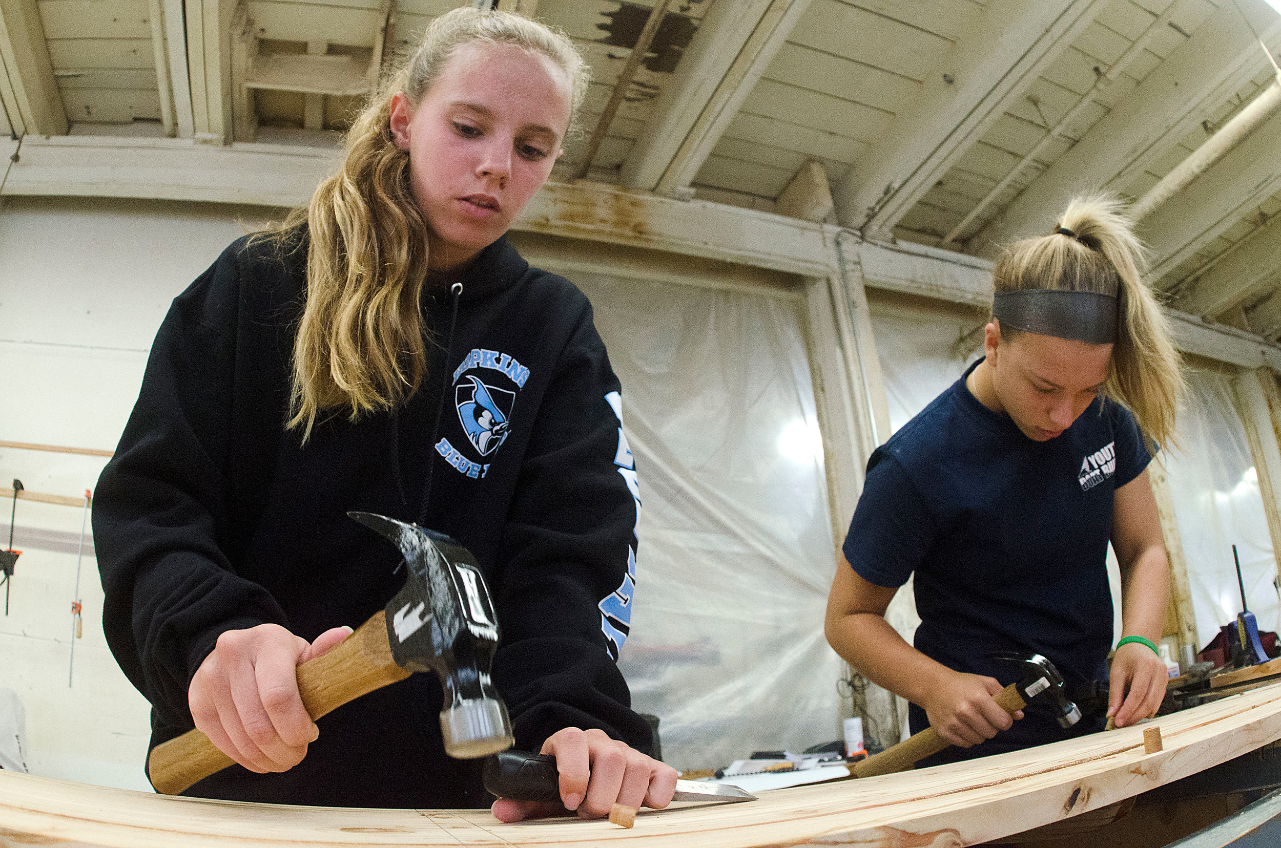 Barrington High School sophomore Claire Grover works with Allison Burke to construct one side of the Westport skiff a group of students are building at Herreshoff Marine Museum.