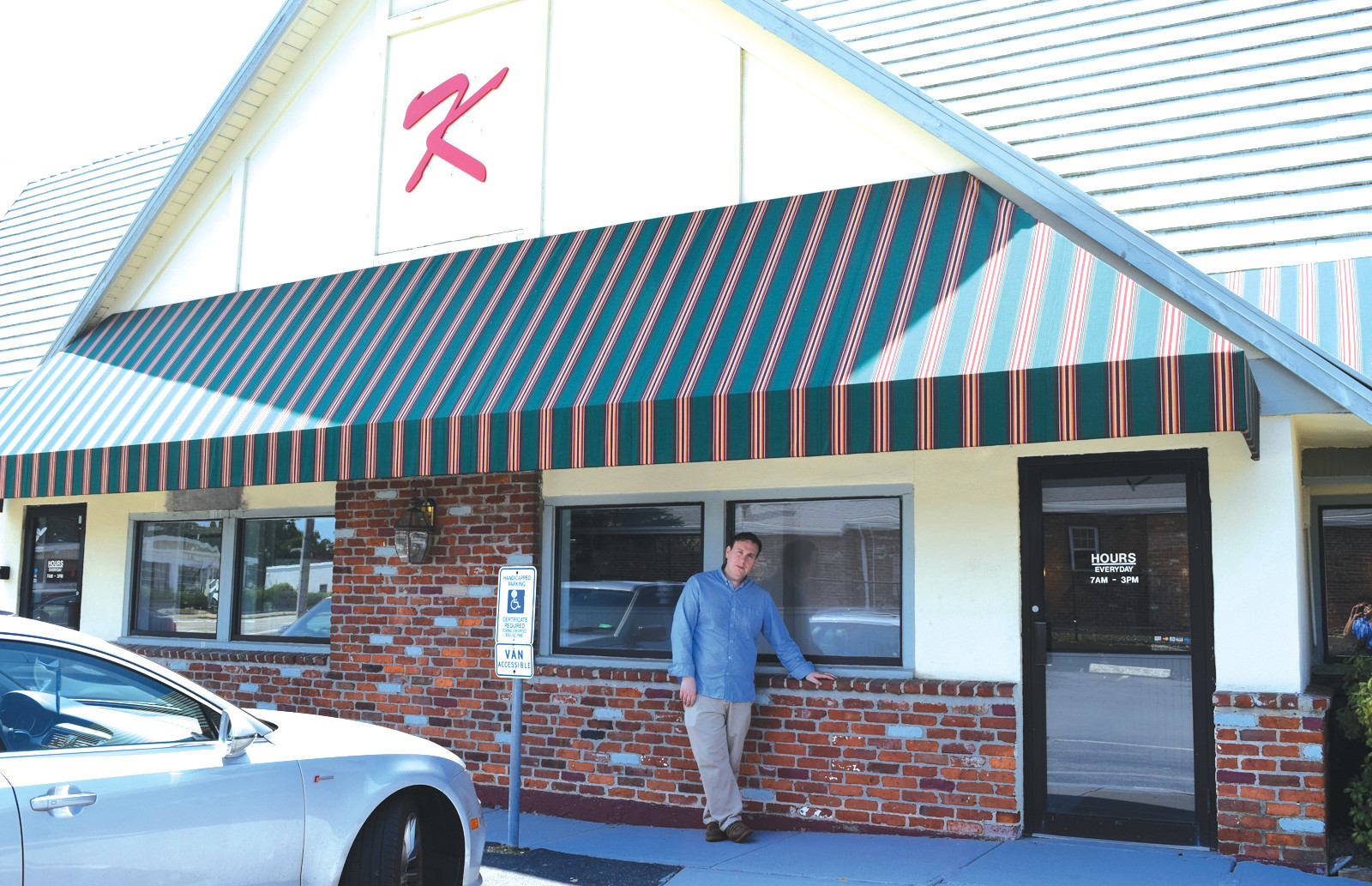 BACK IN BUSINESS: Above, Kenny DeMarco, Jr., leans outside of his establishment, Kenny's Place, which now sports a 'K' on the side of the building.