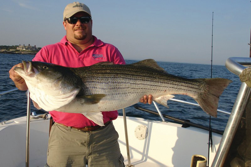 REELING THEM IN: Capt. Eric Thomas of Teezer Fishing Charters with a 40-pound Newport shoreline striped bass he caught 'fishing the wash.'
