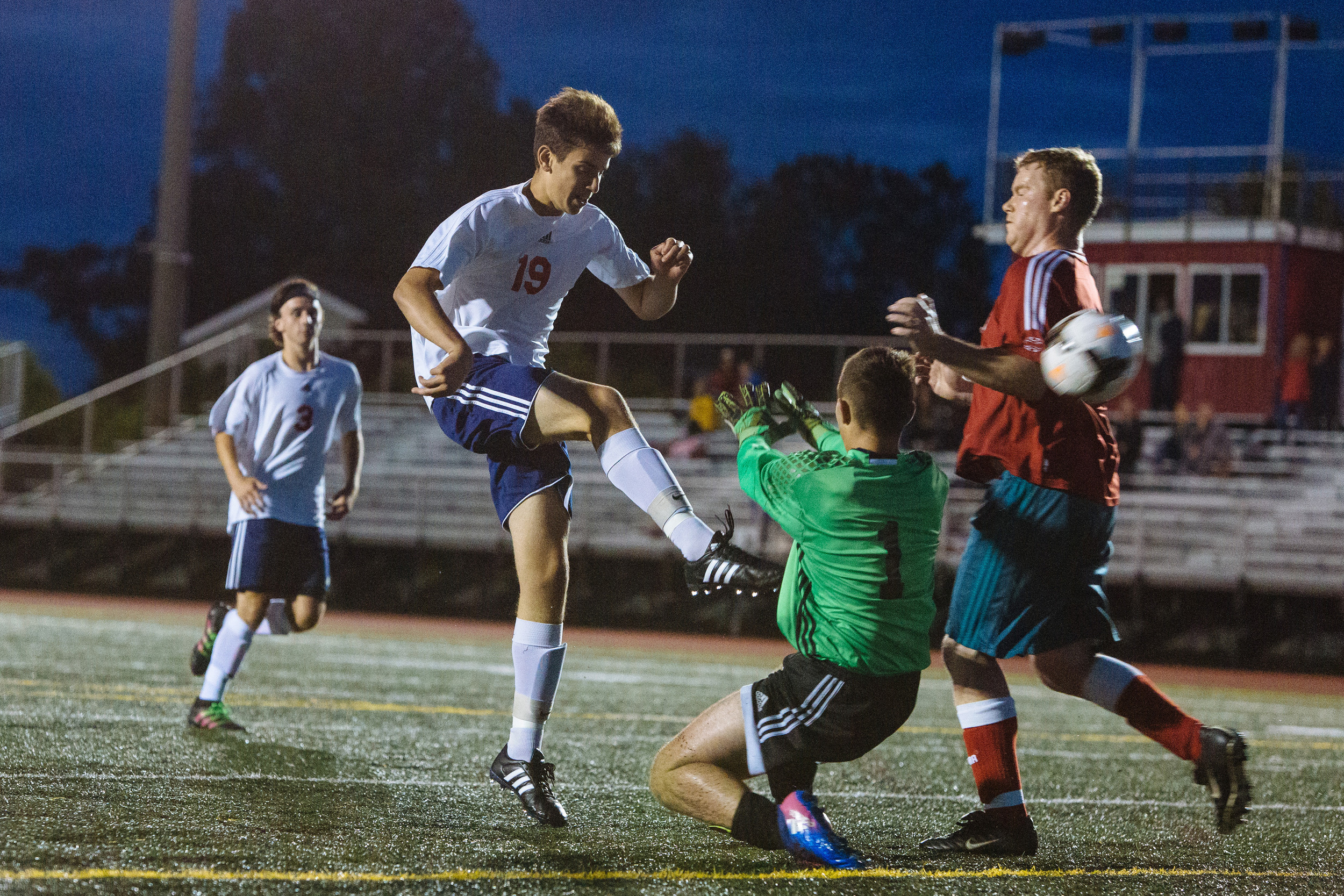 Junior Alex Karousos kicks the ball past goalkeeper Nathaniel Davies of the alumni team. At right is Davies' teammate, Nick Brown.