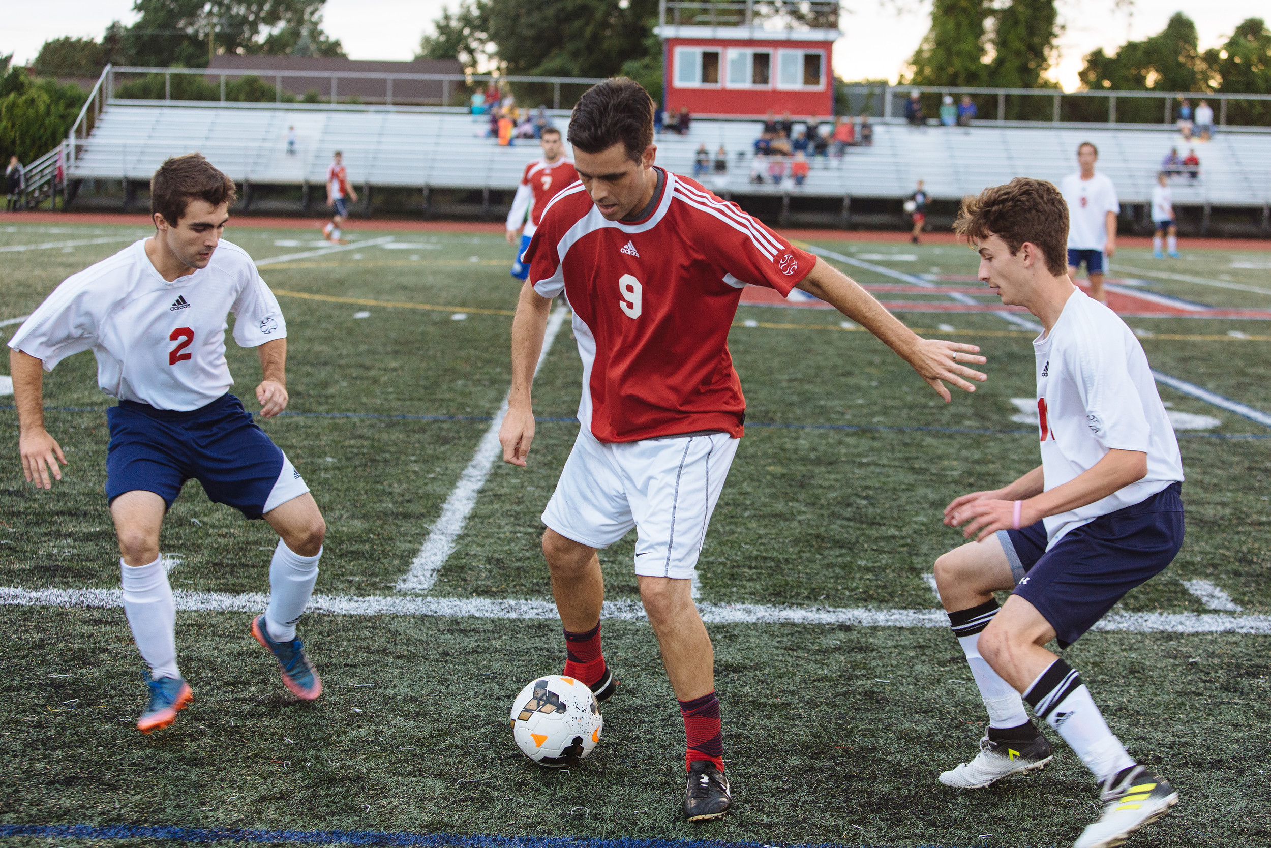 Alumni team member Brian Rosa (center) maintains control of the ball against seniors Kenneth Armijo (left) and Jimmy Baronian of the PHS team.