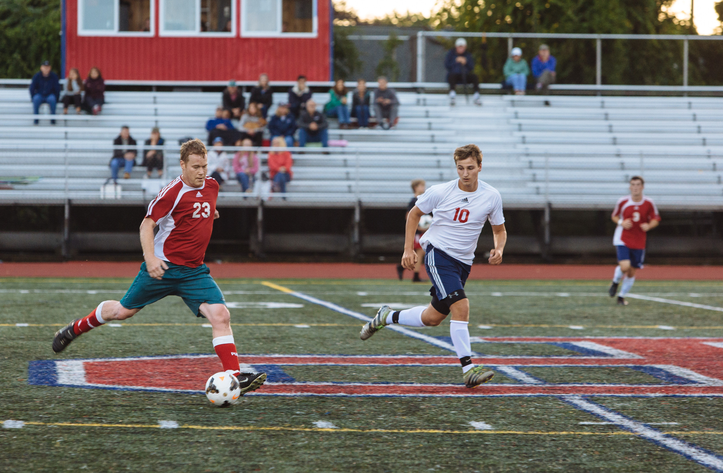 Nick Brown of the alumni team moves the ball downfield while being defended by PHS senior Andrew Maiato.