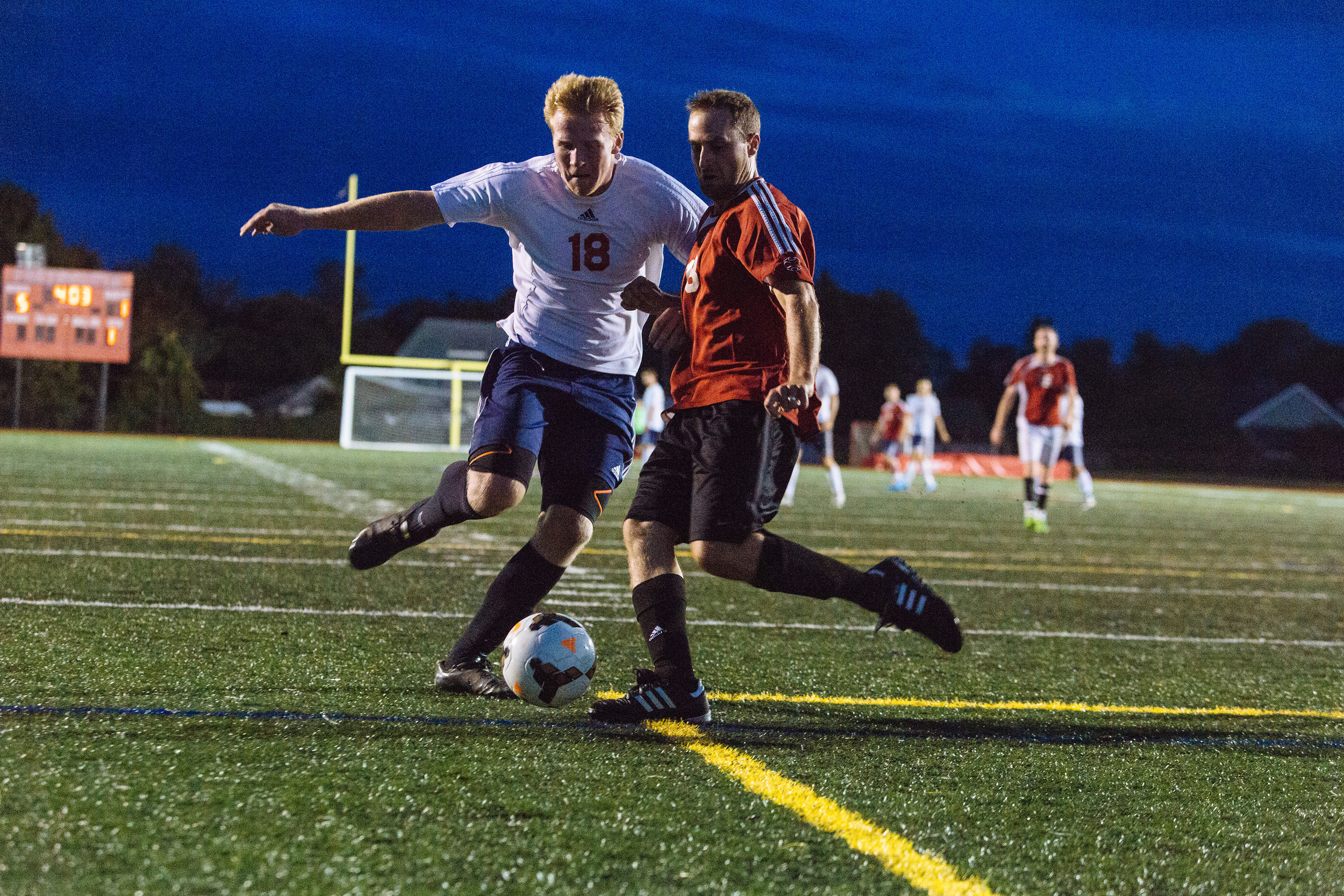 PHS senior Will Swart (left) battles for the ball with Sean Raymond, a member of the alumni team.