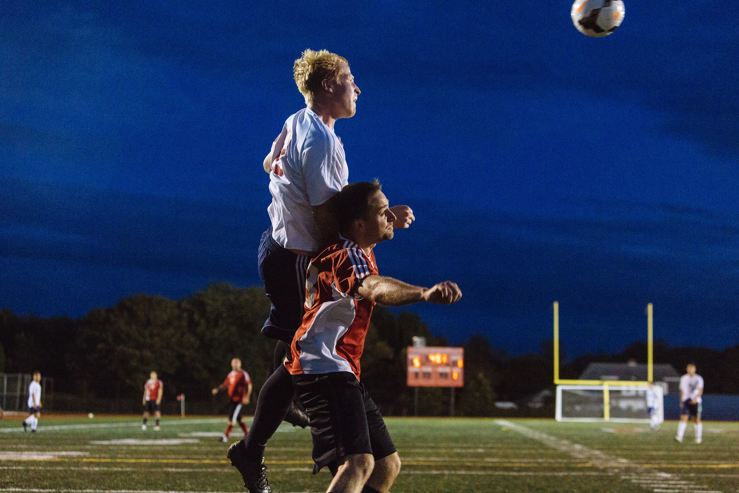 PHS senior Will Swart (left) heads the ball away from defender Sean Raymond, a member of the alumni team.