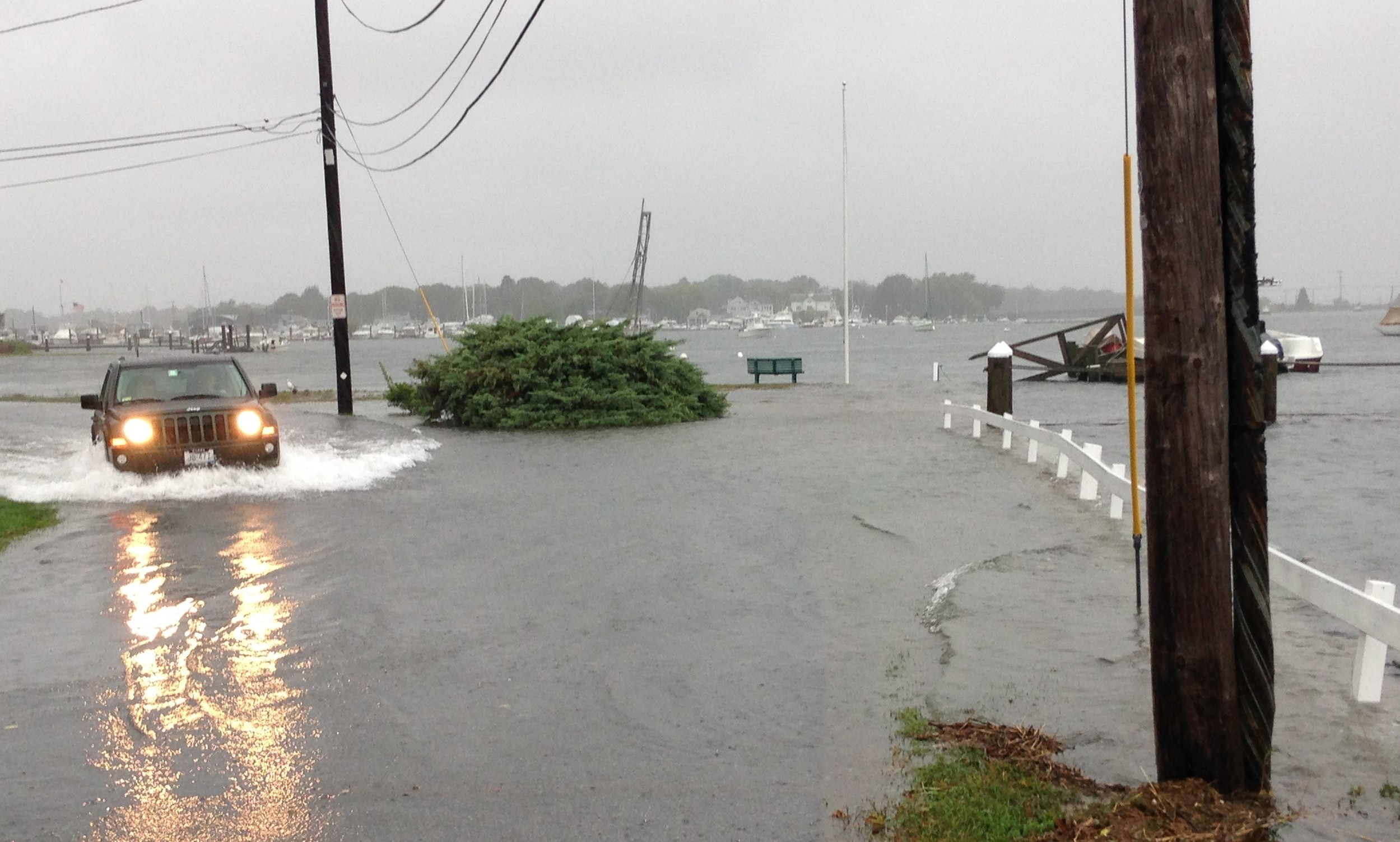 "The Warren River breaches the seawall and swamps yards along Mathewson Road during a rain storm in 2015. ""If we had a category three or four hurricane here, we would become a town of a thousand islands,"" said town manager Jim Cunha."