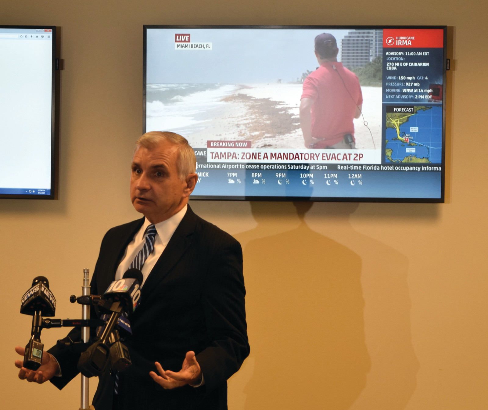 Sen. Jack Reed speaks to the media at R.I. Emergency Management Agency headquarters in Cranston on Friday as the Weather Channel shows Florida bracing for Hurricane Irma in the background.