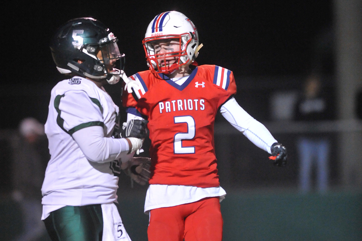 Portsmouth's Connor Stone (right) gets wrapped up by Cranston East's Rayveon DeOliveira after the Patriots' final drive stalled short Saturday night.