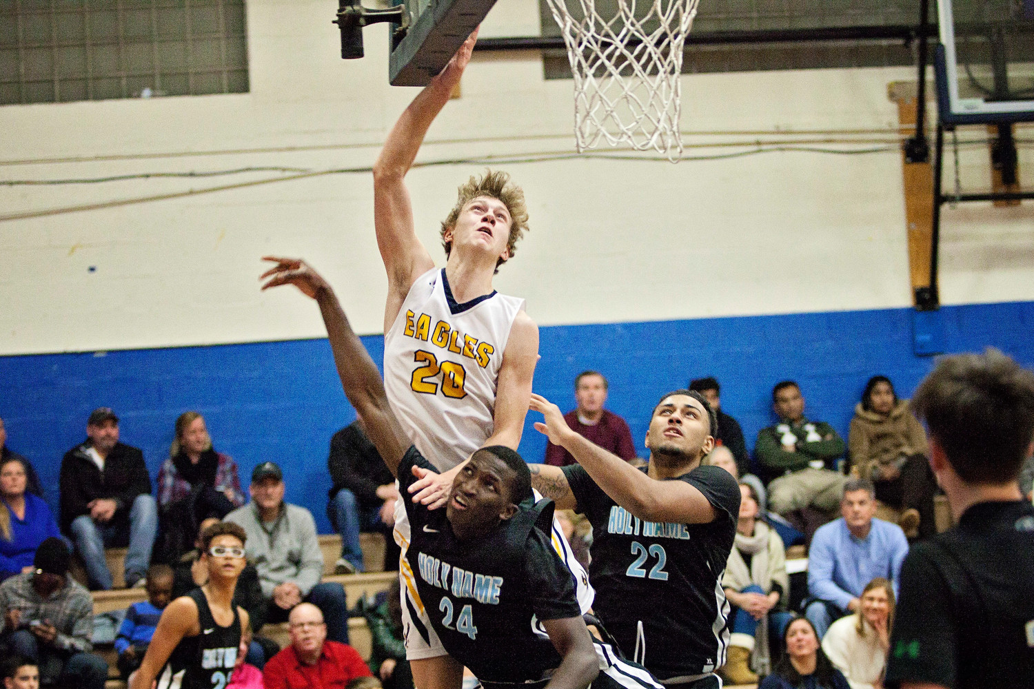Deven Connors elevates over a pair of Holy Name defenders during the Eagles' 70-55 win over Wednesday night.