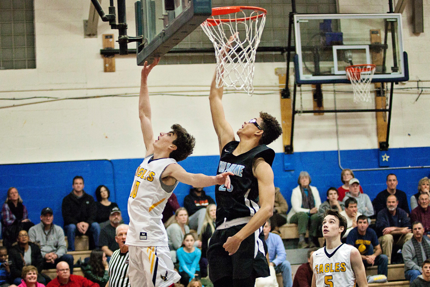 Ryan Bonneau lays the ball up while a Holy Name player tries to block the shot.