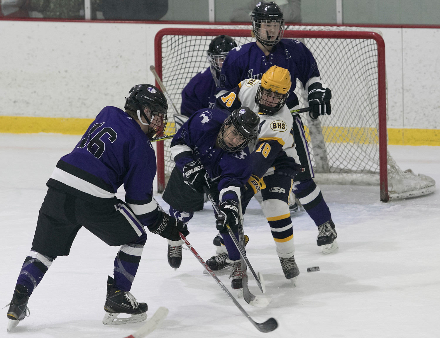 Huskies from left, Devin Lannan, Dave Benevides and Evan Payne helpout goaltender Jack Serbst in front of the net.