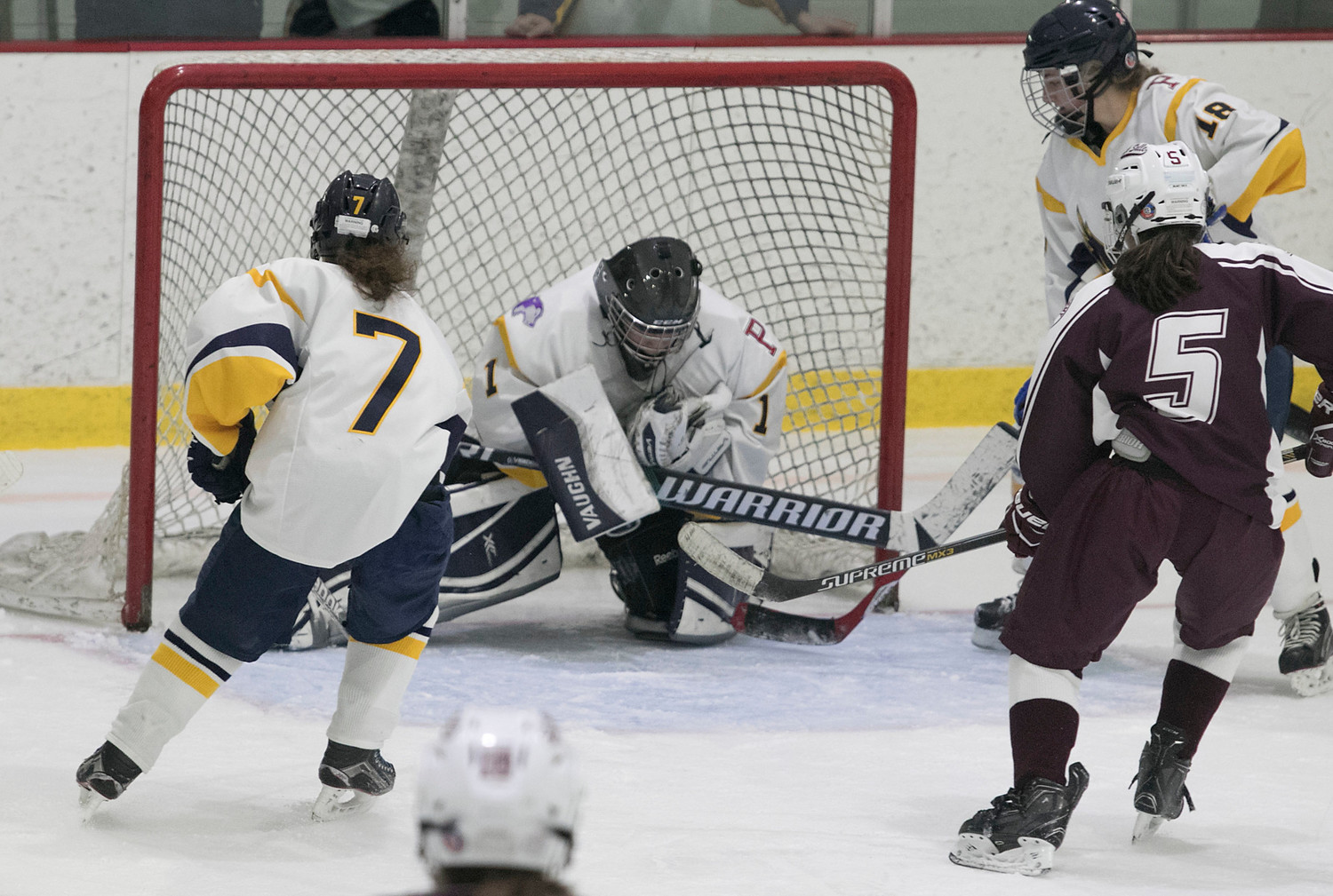 Eagles goaltender Ellee Kopecky makes a save as she's framed by senior forward Sydney Parkhurst (left) and defenseman Ella Hanley (right).