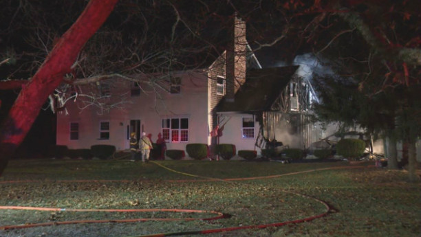 Firefighters hose down the smoldering garage early Thursday morning. The main house was saved. Photo by WPRI TV12.