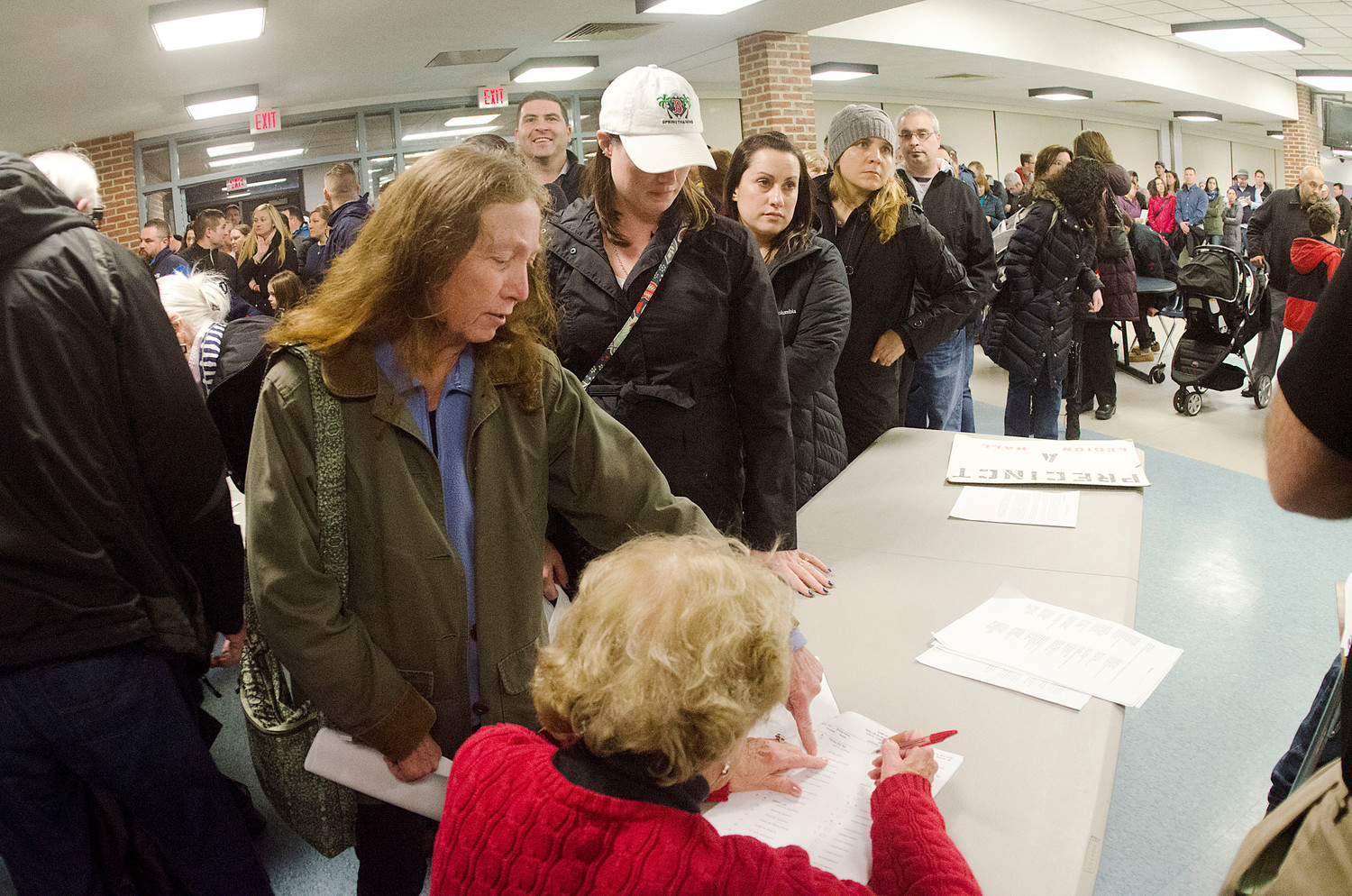 Kathleen Cummings (left) signs in before the meeting. It took over an hour to sign in the 1000 plus voters.
