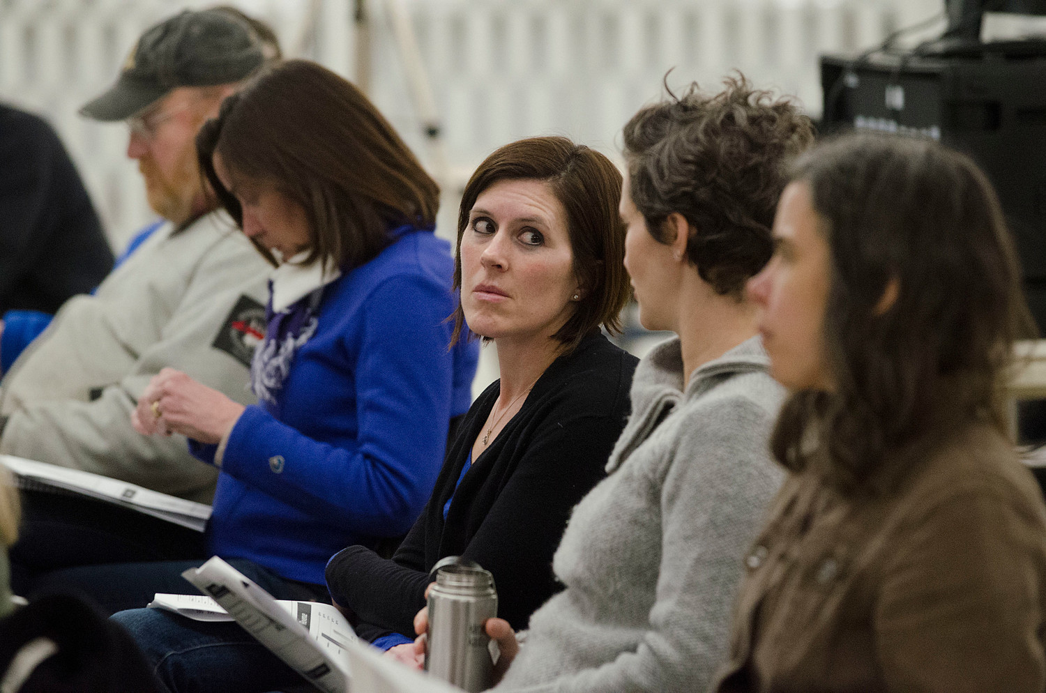 Sally Deal (middle) looks at friend Carly Reich as they react to remarks during the meeting.