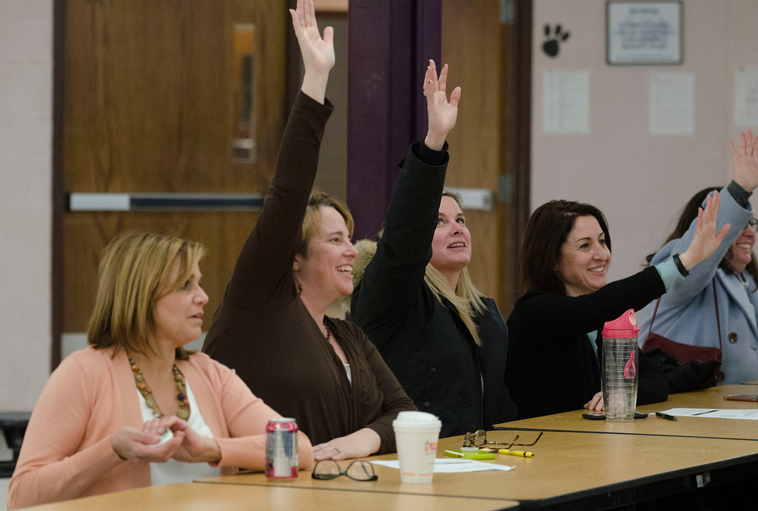 From left, Nicki Tyska, Marie Knapman, Shelia Ellsworth, Amy Bratos and others give a show of hands for those who would go to the state house in an attempt to gain more funds from the state.
