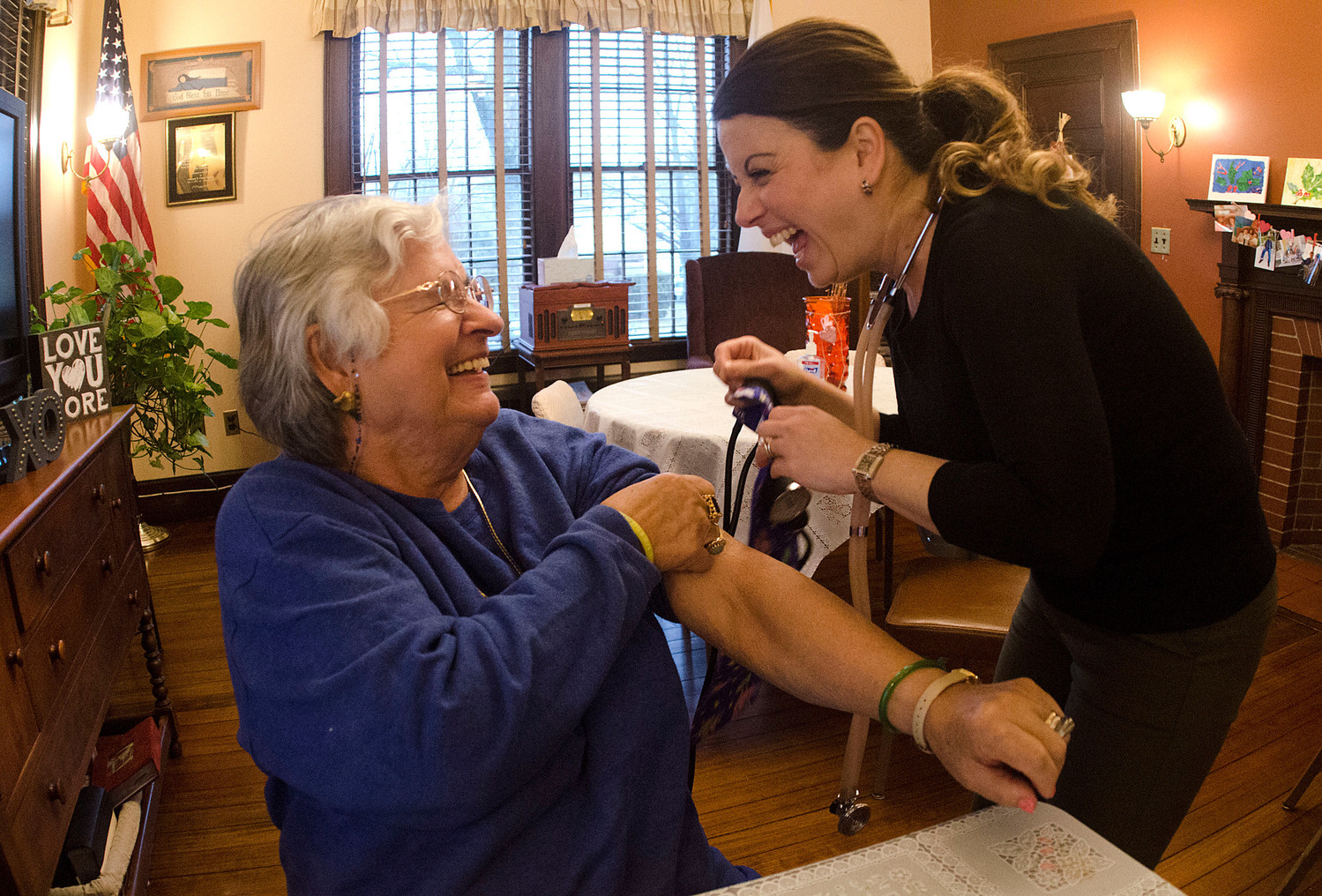 Maria Rodrigues (left) shares a laugh with registered nurse Paula Lage of Willows at Grace Barker during a blood pressure screening before lunch at the Benjamin Church Senior Center.