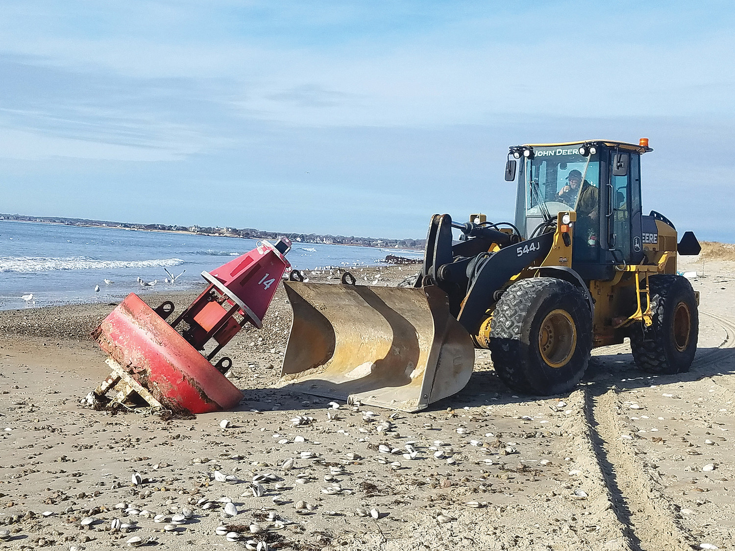 A Highway Department front end loader drives up to beached buoy #14, high and dry on the outer beach south of Bridge Street last week. Westport Marine Services photo.