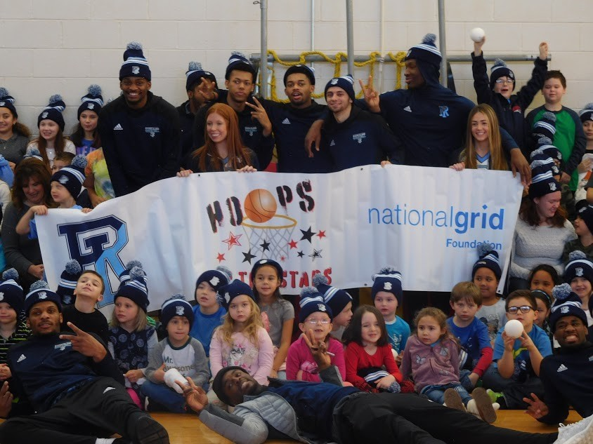 URI team members (that's Stanford Robinson lying across the foreground) and cheerleaders pose for a group shot and a 'Let's Go Rhody'  chant with their Pocasset School fans.