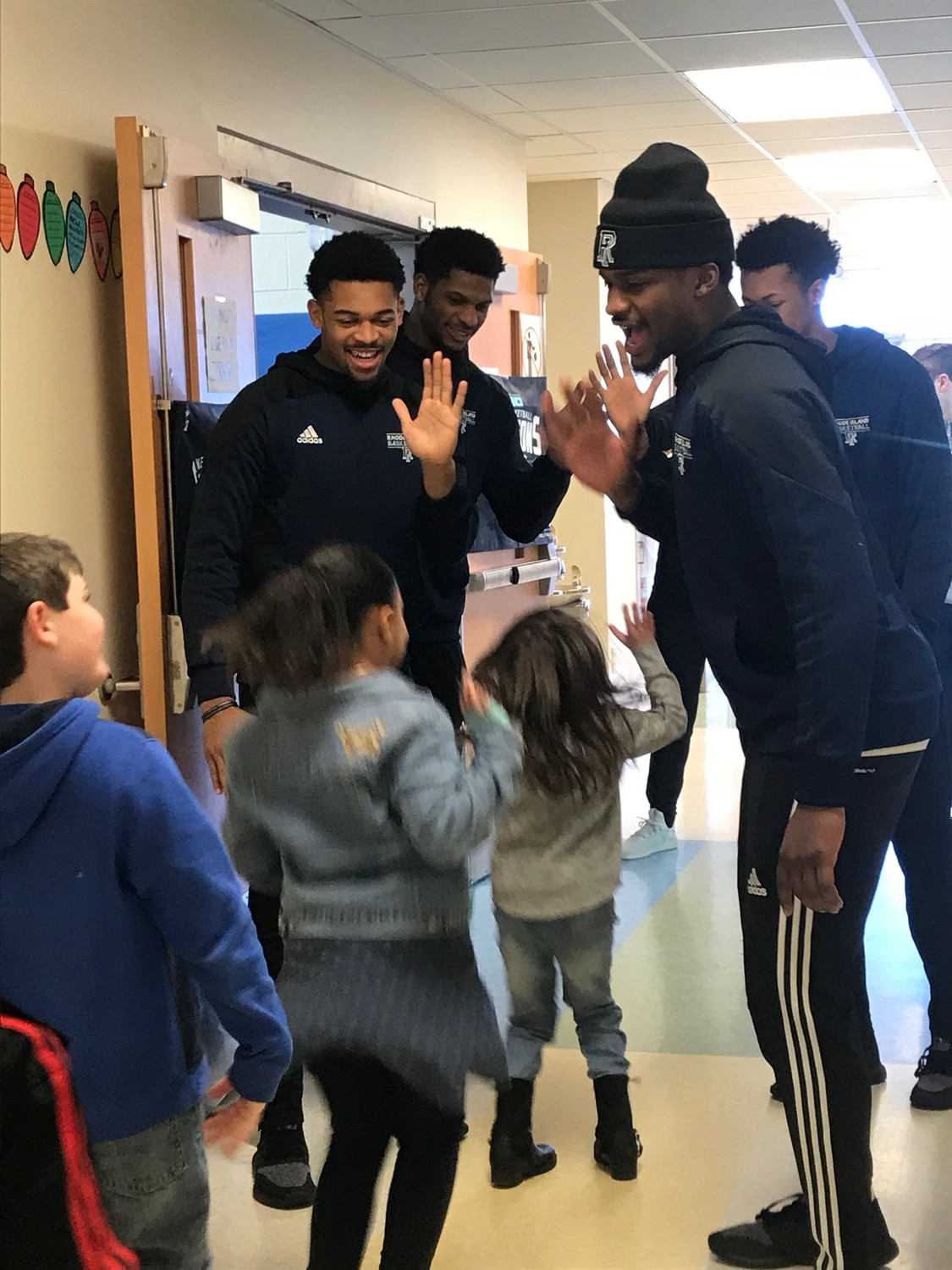 URI hoops stars welcome Pocasset students to morning assembly with a 'high-five tunnel.""